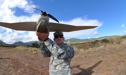 A soldier holding a model of a quieter drone.
